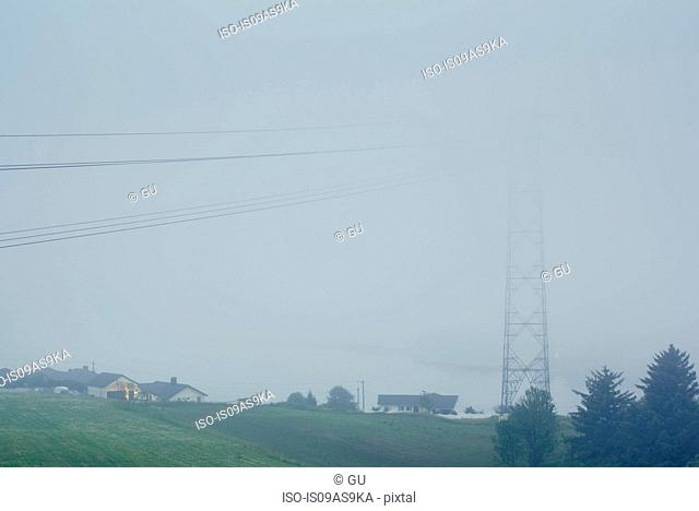 Misty view of electricity cables and pylon next to houses, Haugesund, Rogaland County, Norway