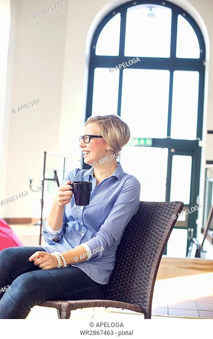 Happy businesswoman holding coffee mug in creative office