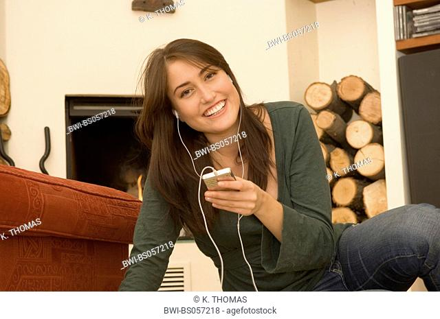 young woman, at home, listening musi with iPod