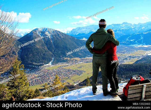 Couple in embrace during winter hike to Schafkopf with a view of Farchant, Orst overview, ski slope still with snow, in the background the Ester Mountains with...