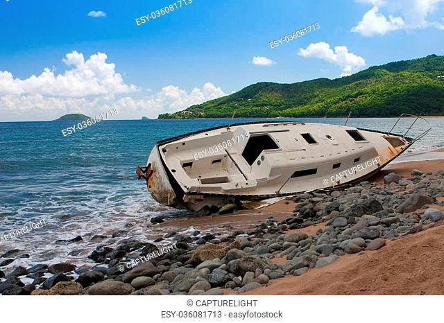 Yacht destroyed after hurricane on the empty beach, Guadeloupe island