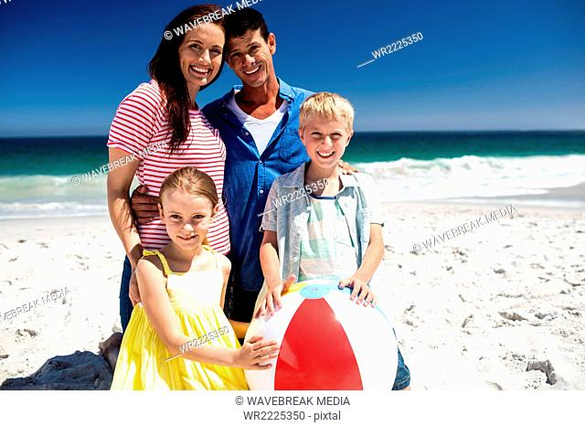 Cute family holding beach ball
