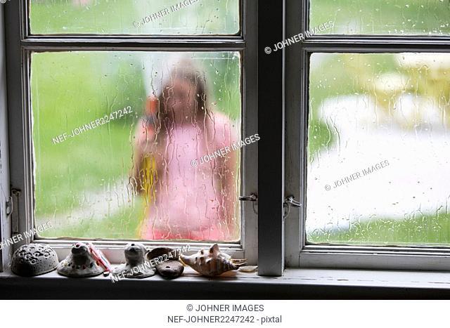 Water on window, girl on background