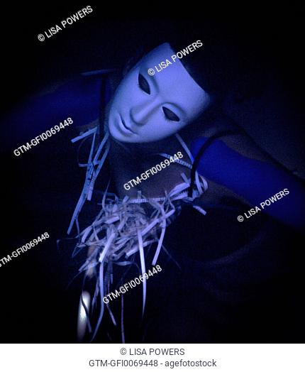 Woman wearing mask holding shredded papers