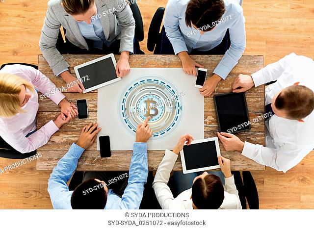 business team with bitcoin holgram at table
