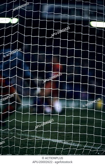 Close up of a goal net with players in background
