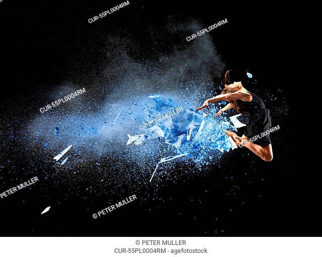 Female dancer mid air with blue powder explosion
