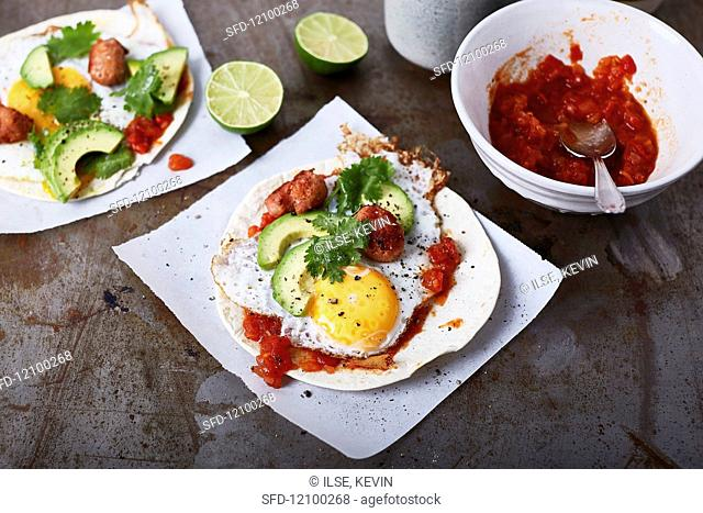 Tacos with avocado, tomato salsa, fried egg and salsiccia