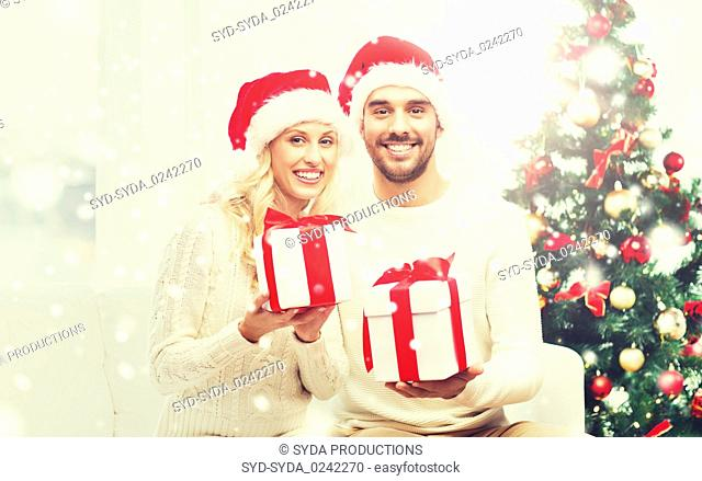 happy couple at home with christmas gift boxes