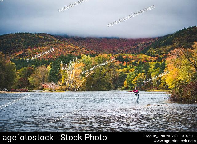 Woman angler casting into river with clouds and bright foliage