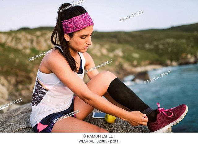 Sportive woman sitting on rocks in the evening