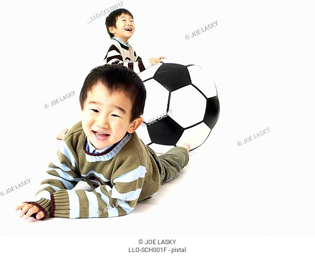 Two Young Boys Playing with a Large Ball  Studio Shot
