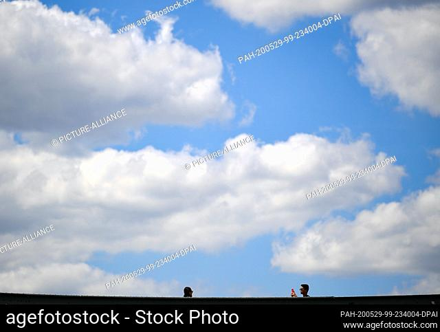 29 May 2020, Hessen, Frankfurt/Main: Clouds drift across the blue sky above the Iron Bridge, where a tourist couple is taking souvenir photos