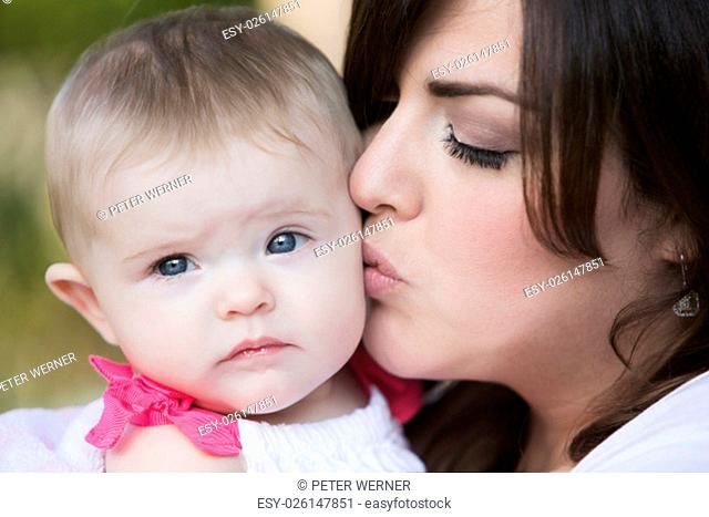 brunette woman kissing her baby on cheek
