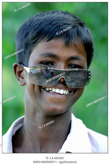 Portrait of a rural boy having fun with a sunglass Chittagong, Bangladesh May 11, 2007