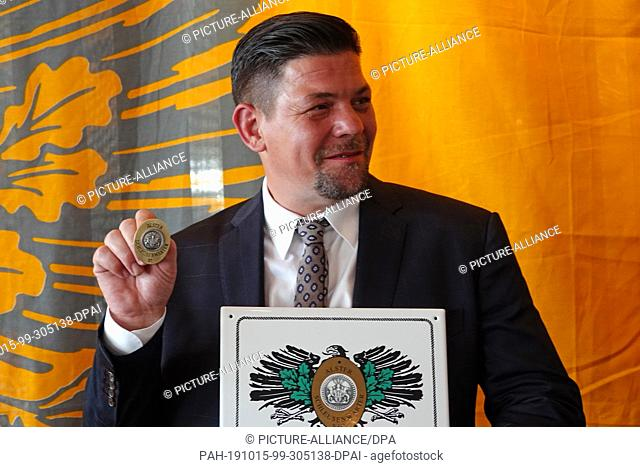 """15 October 2019, Hamburg: TV chef and restaurateur Tim Mälzer holds up his medal """"""""Alster lockkeeper"""""""". Mälzer was appointed as the new Honorary Lockkeeper by..."""