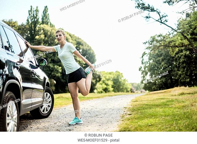 Sportive young woman stretching at a car in a park