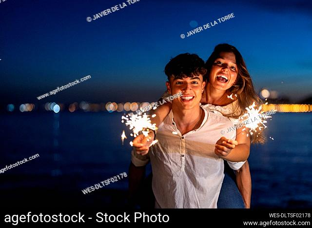 Happy young brother giving piggyback ride to sister holding sparklers at beach