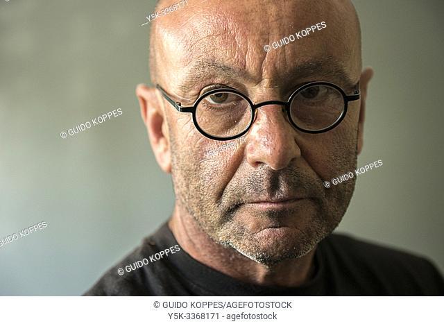 Tilburg, Netherlands. Studio portrait with natural light of a balding, mature adult man wearing glasses