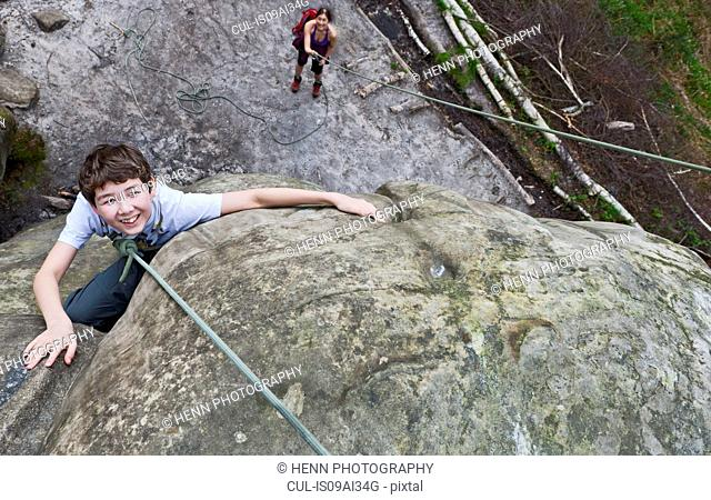 High angle view of boy rock climbing boulder