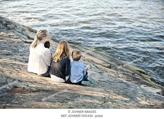 Mother with three children sitting at water, Nacka, Sweden