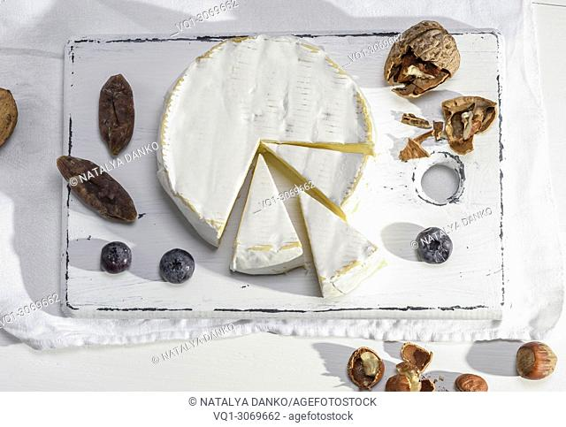 round piece of camembert cheese on a white wooden board, top view