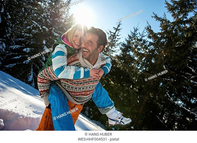 Austria, Salzburg, Man giving piggyback ride to woman, smiling