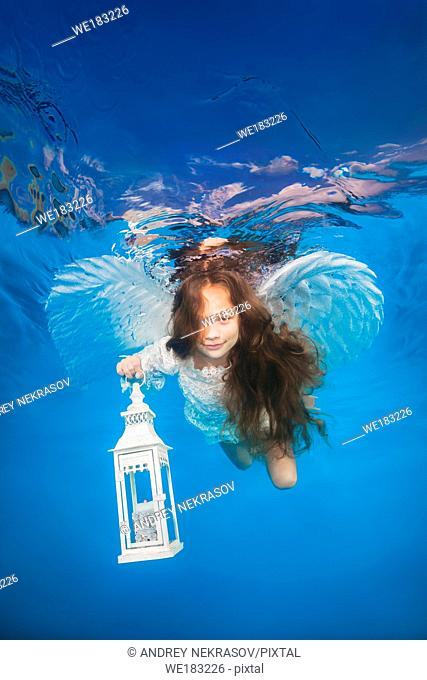 White angel with a flashlight underwater. Underwater girls pictures