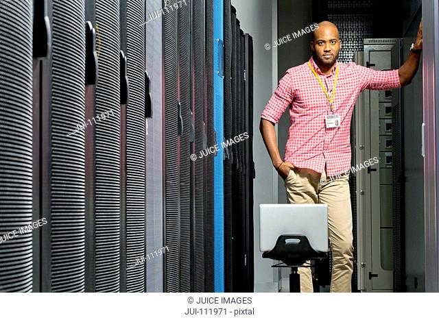 Technician with laptop looking at camera in server data centre