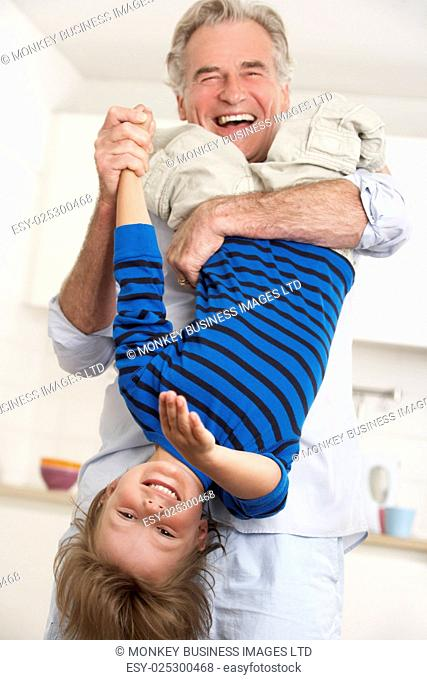 Grandfather Holding Grandson Upside Down At Home