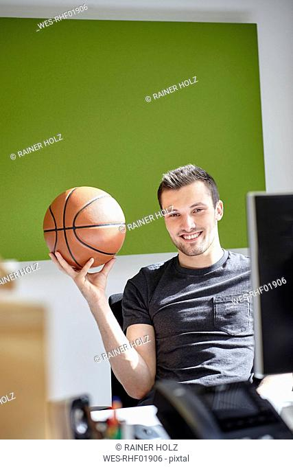 Young man working in office, balancing a basketball