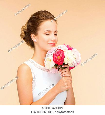 happiness, wedding, holidays and celebration concept - smiling bride or bridesmaid in white dress with bouquet of flowers