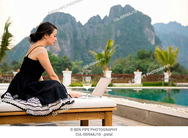 Woman using laptop by poolside, Vang Vieng, Laos