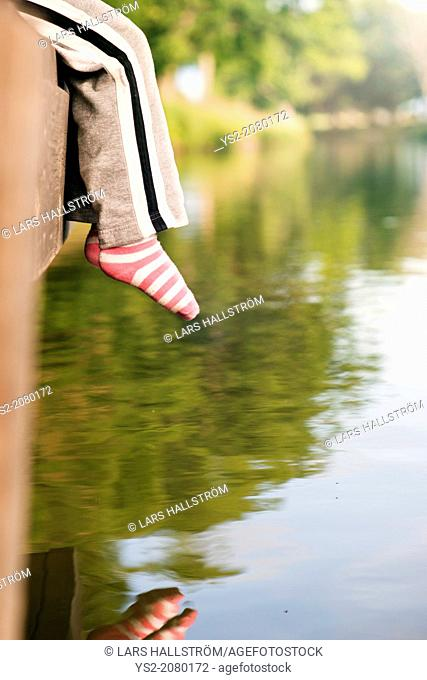 Lifestyle moment of summer childhood. Little girl sitting on jetty by canal