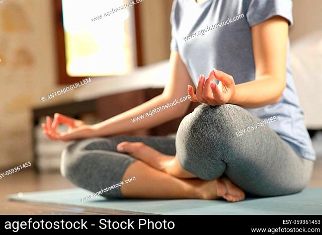 Close up of a woman doing yoga exercise on the floor at home