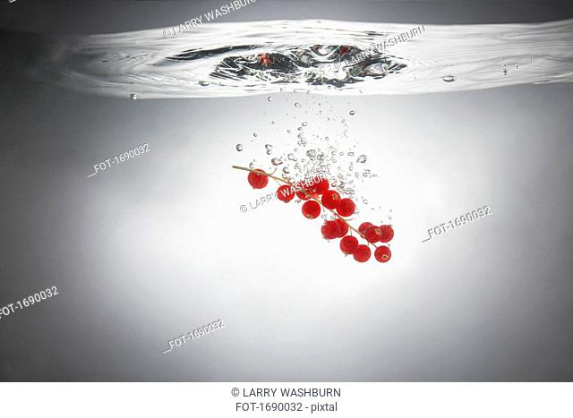 Close-up of red currants in splashing water