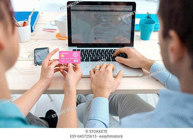 Married couple shopping online at home, he is typing on a laptop, his wife is holding a credit card, spending and telecommunications concept