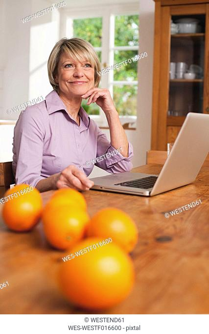 Germany, Kratzeburg, Senior woman with laptop and fruits on table in foreground
