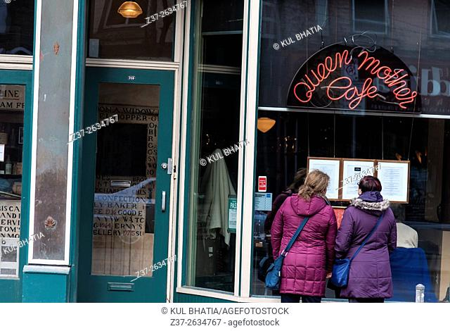 Two women looking at the menu posted outside a trendy cafe, Toronto, Ontario, Canada