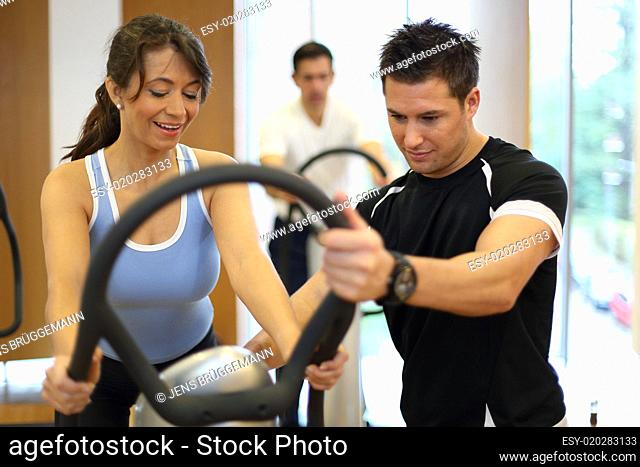 Personal trainer explaining a vibration plate in a gym to a fema