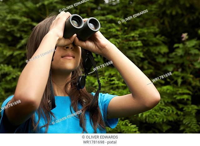 A young girl with bird watching binoculars