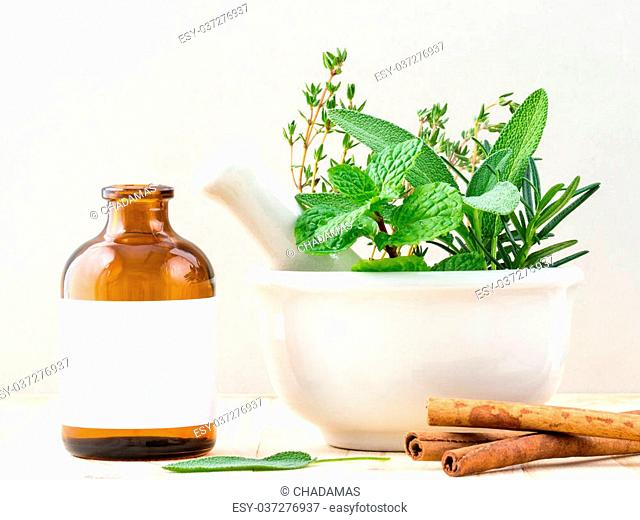 Alternative health care fresh herbal and Bottle of aromatherapy in mortar on wooden background