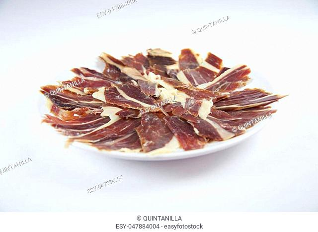 pile of typical spanish iberico ham sliced on white dish