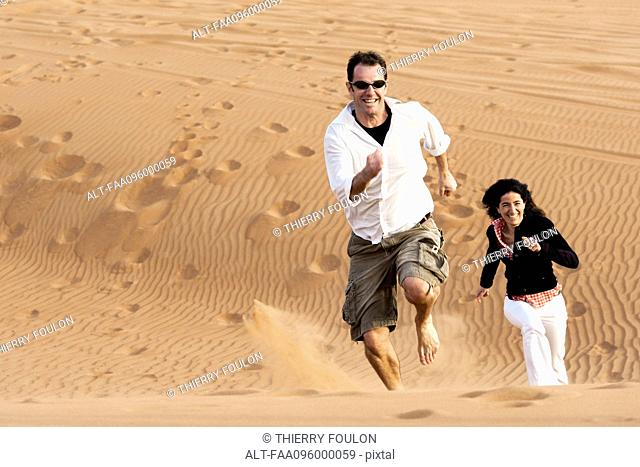 Couple running up desert dune