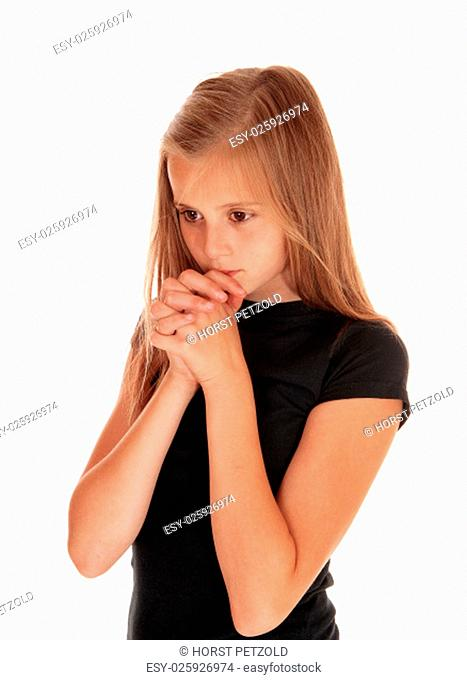 A pretty girl in a black sweater with her hands folded and praying, standing.isolated for white background.