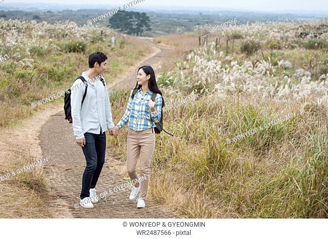 Young smiling couple walking holding hands face ro face in silver grass field
