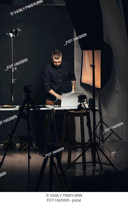 Photographer working on laptop while standing by food plate against backdrop at studio