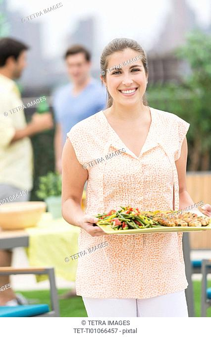 Woman carrying tray with food in garden