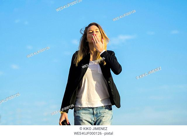Woman standing in front of blue sky blowing a kiss to viewer