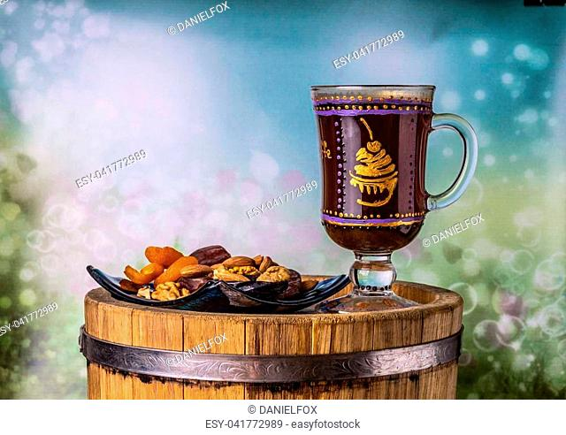 Coffee with dried fruit on an oak barrel, on a color background